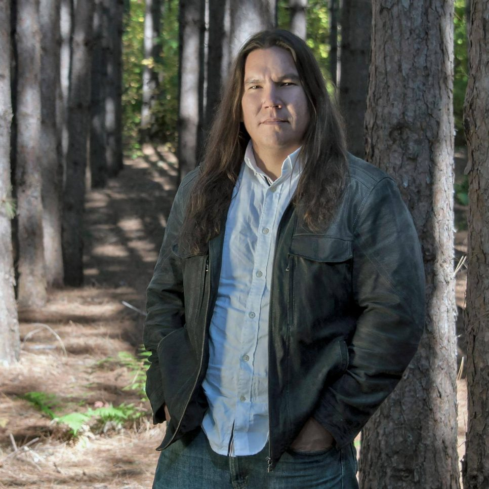 A First Nations man stares straight into the camera with a small frown. He's in a wooded area with sunlight seem on the tree branches. He has long, straight brown hair and it wearing a denim shirt and a long sleeve dark grey jacket.