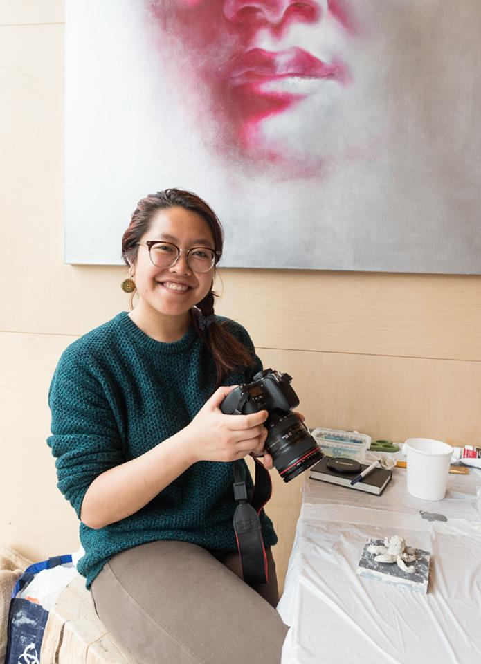 Christie Wong sits on a stall by a table covered in cloth, holding a DSLR camera and smiling at the lens of the camera taking the photo. She is an Asian women wearing round, wooden earrings, round glasses, a green sweatshirt and grey/beige pants.