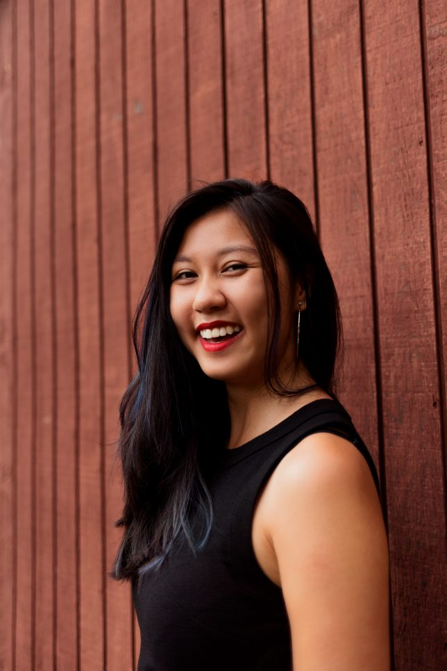 Linh, an Asian woman with chest-length black hair, is looking at the camera from the side. She stands by a wooden-paneled wall and is smiling with her mouth open. She's wearing a black, sleeveless shirt and red lipstick.